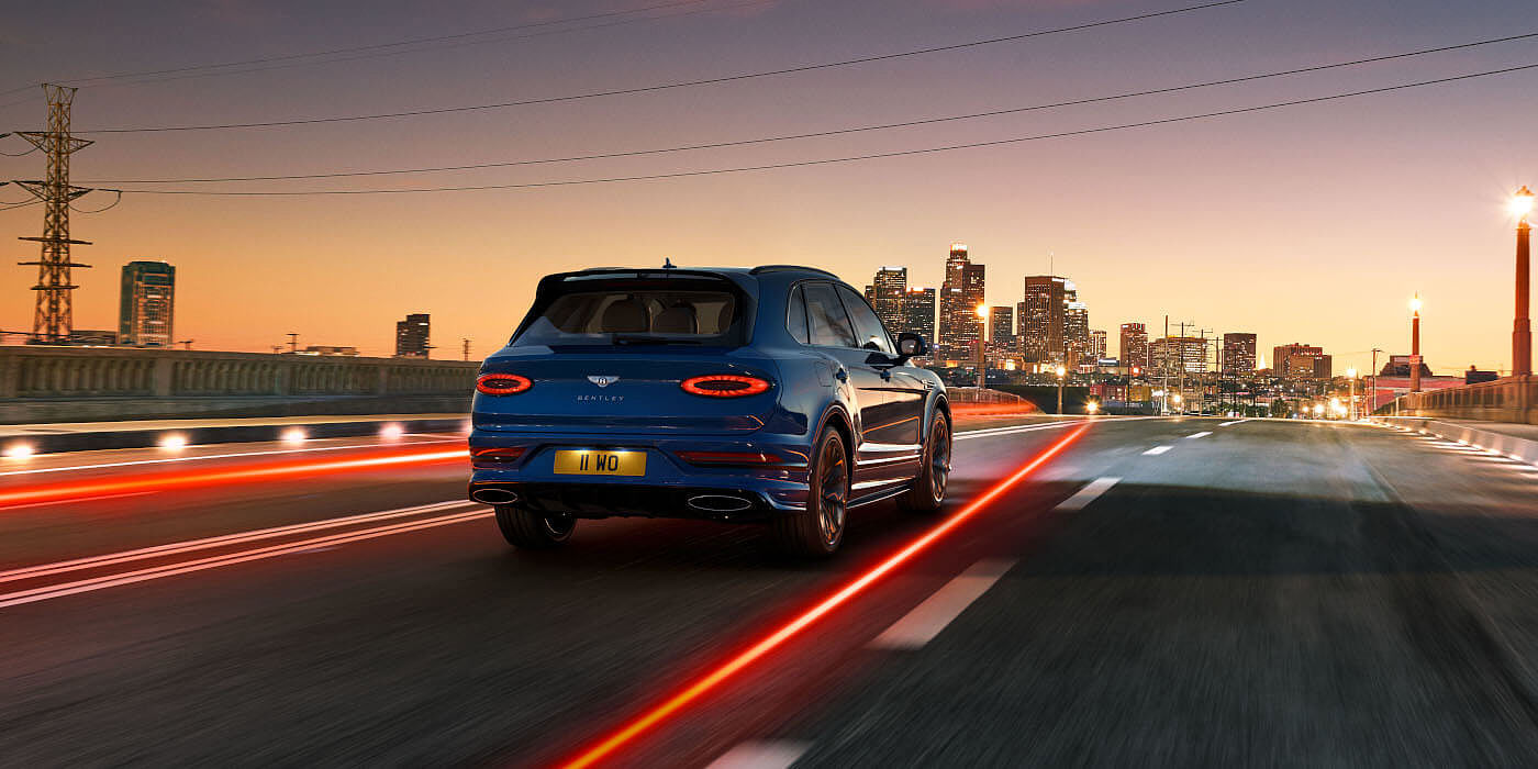 new-moroccan-blue-bentley-bentayga-speed-rear-three-quarter-driving-towards-city